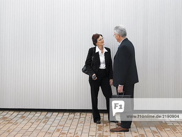 Geschäftsleute an einer silbernen Wand.