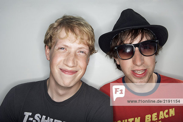 Two young males one wearing glasses and hat