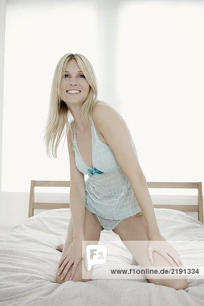Porträt einer Frau auf dem Bett.
