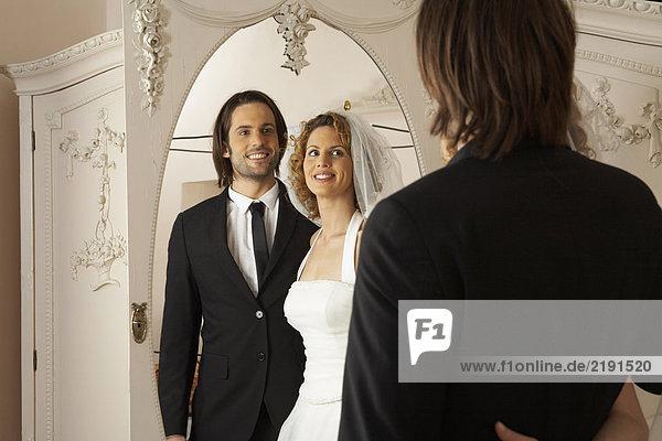 junges Brautpaar lächelt bei der Spiegelung