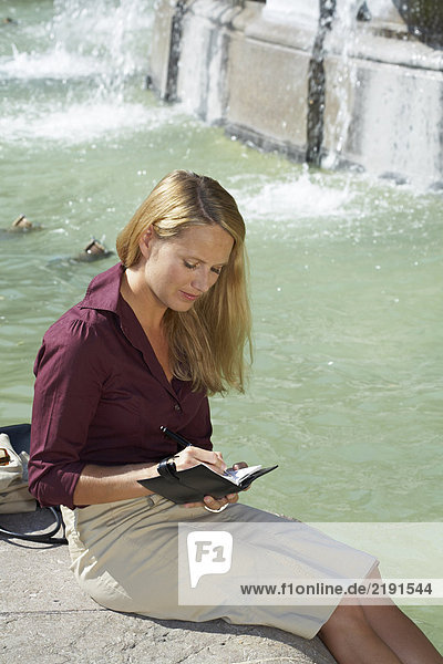 Businesswoman sitting on fountain flipping through agenda laughing.