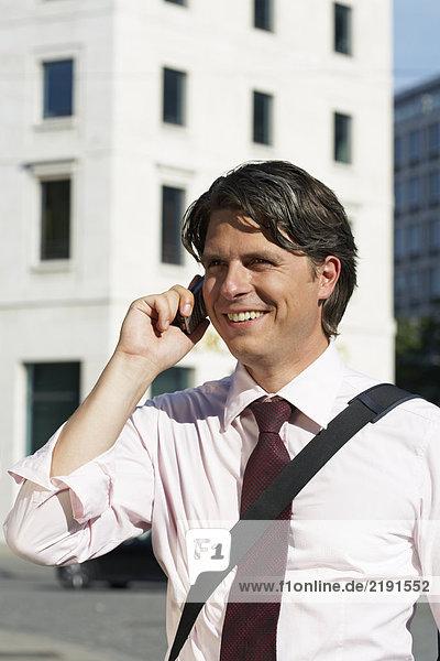 Glücklicher Geschäftsmann am Handy.