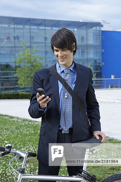 Businessman holding bike and looking at cell phone.