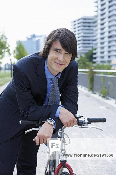 Businessman in park resting on bike smiling portrait.