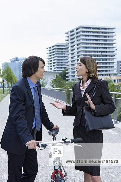 Businessman and woman discussing in-between bike.