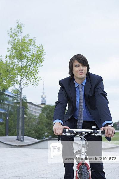 Businessman on bike laughing.
