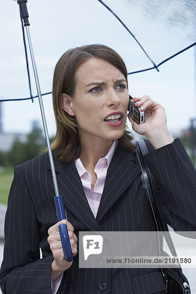 Angry businesswoman under umbrella on cell phone.