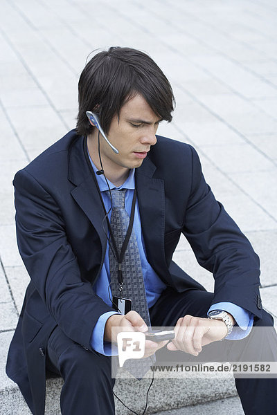 Businessman sitting on steps looking at his watch with headset and mobile.