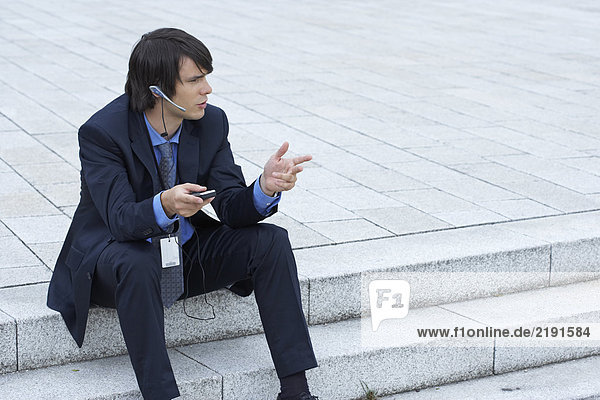 Businessman sitting on steps with headset and mobile discussing looking into distance.