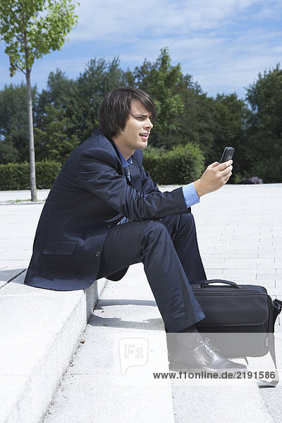 Businessman sitting on steps looking at his mobile view from side park in background.