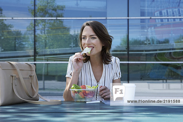 Businesswoman on table in front of office outside biting off salad to go.