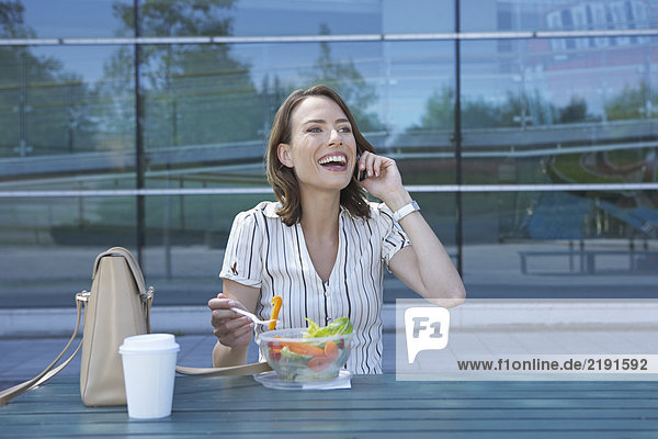 Businesswoman on table in front of office outside on the mobile whilst eating salad to go looking up smiling.