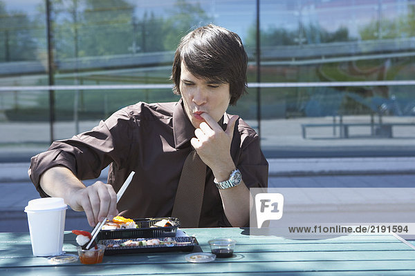 Businessman on table in front of office outside with sushi lunchbox and sticks licking off his finger.