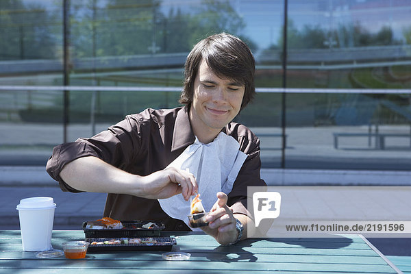 Smiling businessman eating sushi with chopsticks outside.