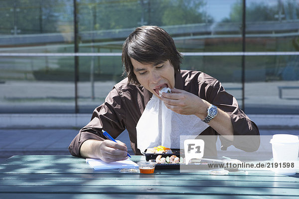 Businessman eating sushi and doing work while outside.