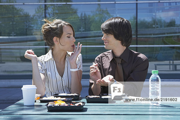 Businessman and woman on table in front of office outside with sushi lunchbox and sticks she is eating he is watching her.