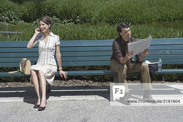 Geschäftsmann und Frau sitzen draußen auf der Bank.