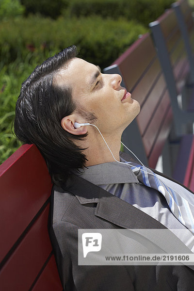 Businessman on bench with MP3 earpieces listening eyes closed close up.
