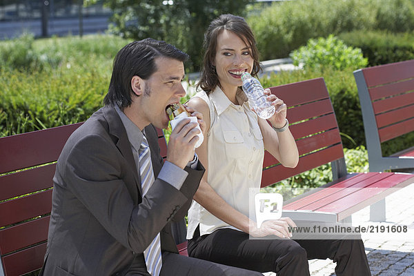 businessman and woman sitting on a bench outdoors she's about to drink water he is having a sandwich