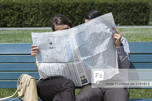 Businessman and woman on bench in park reading a newspaper together hiding behind.