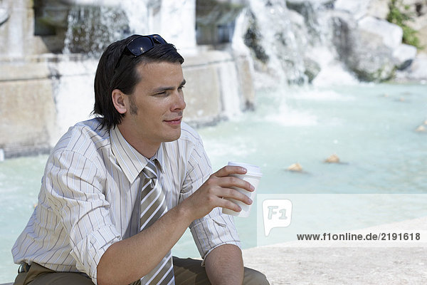 Businessman sitting on edge of fountain holding a coffee to go smiling portrait.