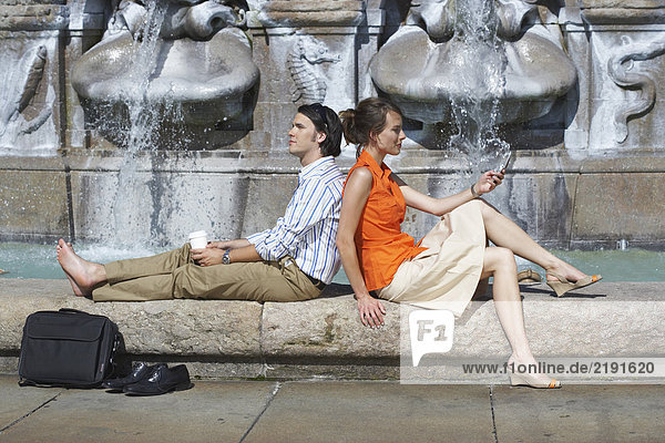 Businessman and woman leaning on each other while sitting on fountain's edge.