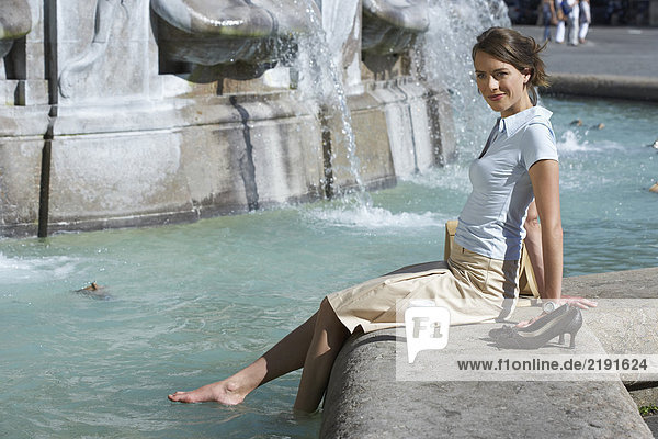 Businesswoman sitting on edge of fountain bare feet in fountain smiling.