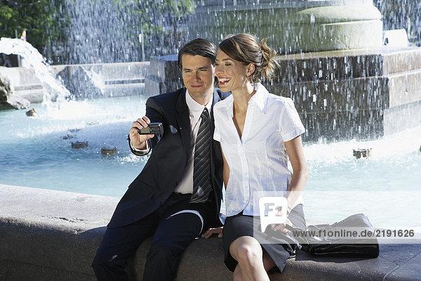 Junges Paar beim gemeinsamen Fotografieren neben dem Brunnen.