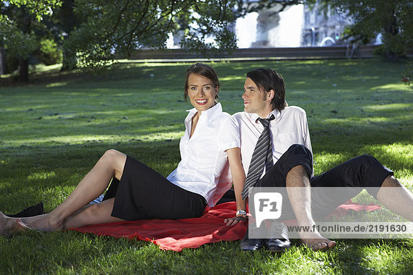 Businessman and woman sitting on blanket in meadow in park both bare feet.