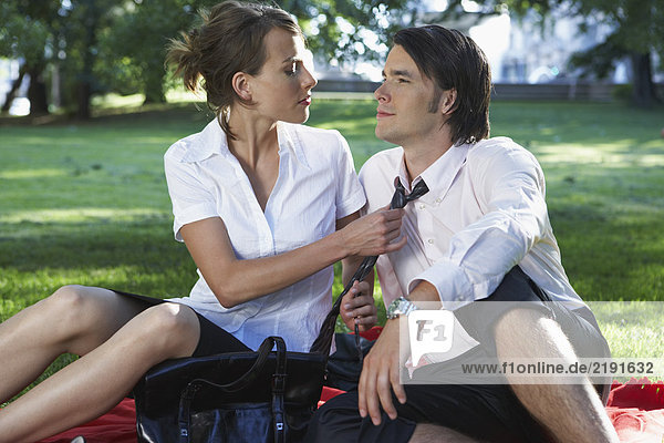 Businessman and woman sitting on blanket in meadow in park she is adjusting his tie.