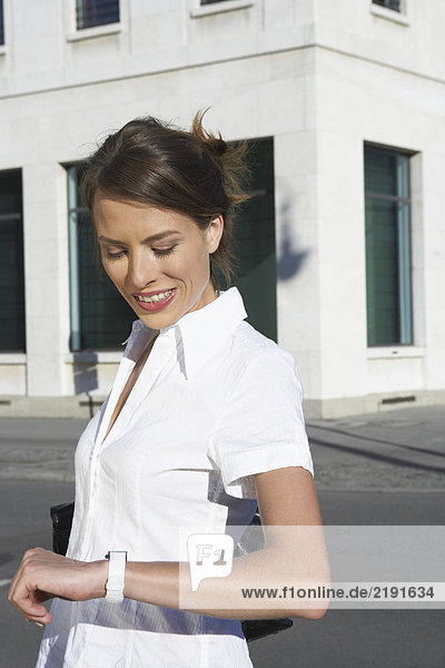Businesswoman standing at square in city looking at her watch smiling.
