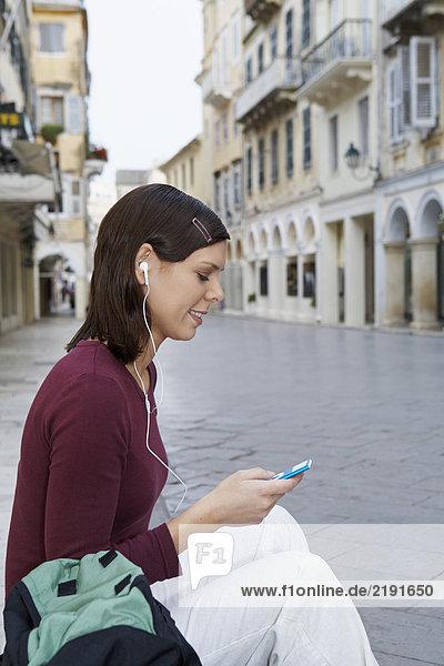 Junges Mädchen sitzt auf Stufen in Straßen-Kopfhörern in Ohren MP3 in der Hand lächelnde Altstadt im Hintergrund.