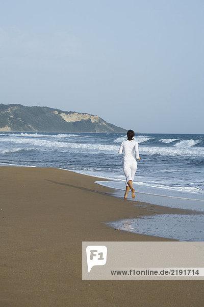 Frau joggt vor der Kamera am Strand.