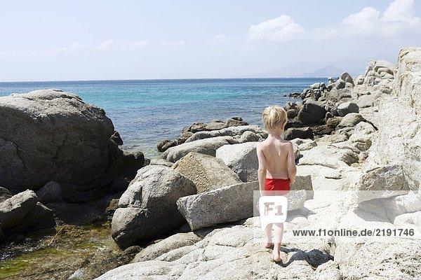 Kleiner Junge  der auf Felsen in der Nähe des Wassers läuft.