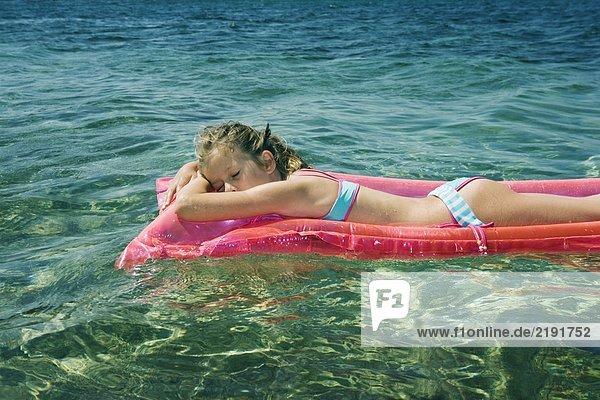 Junges Mädchen  das auf einem aufblasbaren Floß schläft.