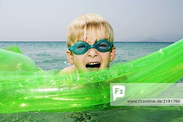 Kleiner Junge mit einem aufblasbaren Floß im Wasser mit offenem Mund.