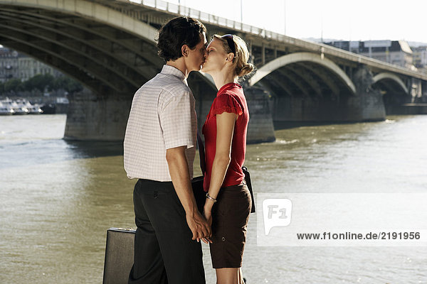 Ein paar Küsse bei einer Brücke.