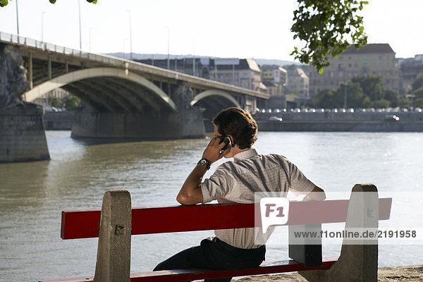 Geschäftsmann sitzt allein auf der Bank am Fluss.