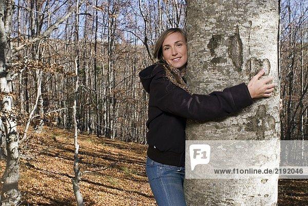 Eine Frau  die einen Baum in die Arme nimmt.