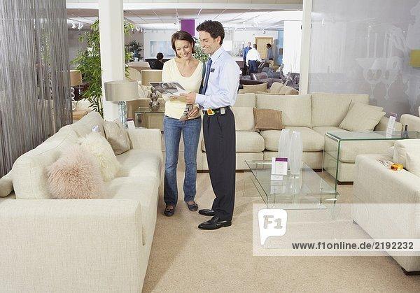 Frau im Gespräch mit dem Verkäufer im Sofageschäft.