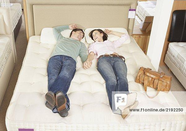 Ein Paar liegt auf dem Bett im Möbelhaus.