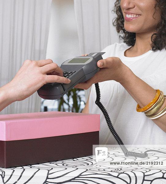 Junge Frau mit Kreditkartenleser für Kunden  Nahaufnahme