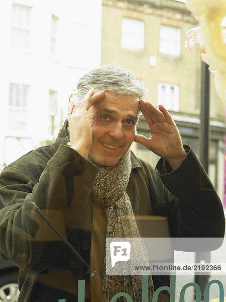 Reifer Mann  der ins Schaufenster blickt  lächelnd