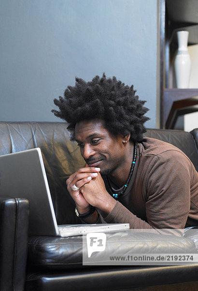 Mann auf dem Sofa liegend mit Laptop