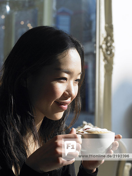 Young woman holding cappuccino  smiling  close-up