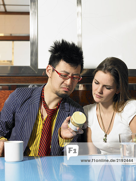 Junger Mann und Frau beim Lesen von Zutaten auf einem Glas im Diner