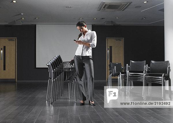 Frau stehend mit Stuhlstapel im leeren Präsentationsraum