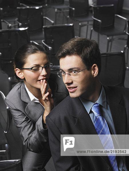 Frau flüstert dem Mann zu  der im Auditorium sitzt.