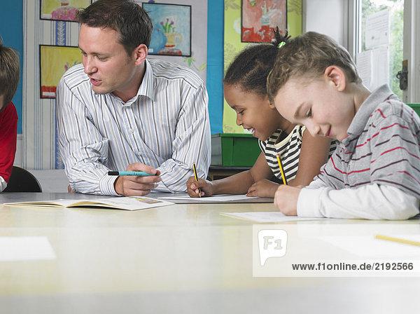 Lehrer am Arbeitstisch sitzend mit Mädchen und Junge