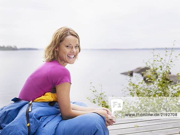 Woman with sleeping bag wrapped around her waist laughing by water.